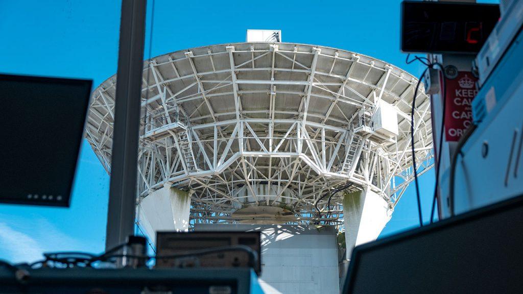 White radar dish with metal supports, viewed through window