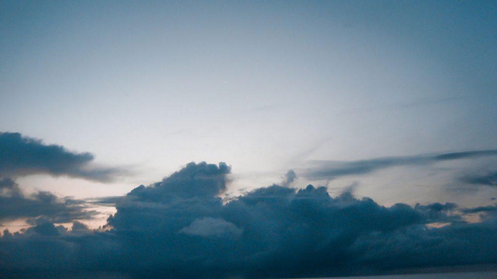 Dark fluffy clouds below a clear sky