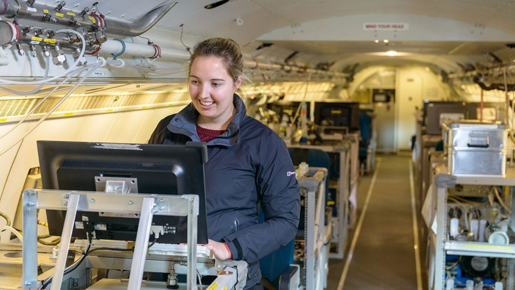 Woman wearing blue jacket stands at a computer desk inside an aircraft full of scientific kit