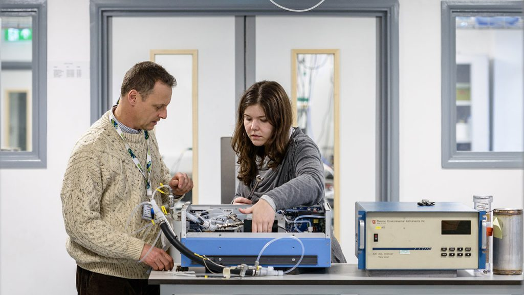 Man wearing beige knitted jumper and female wearing grey jumper stand at a desk, inspecting a blue machine with wires.