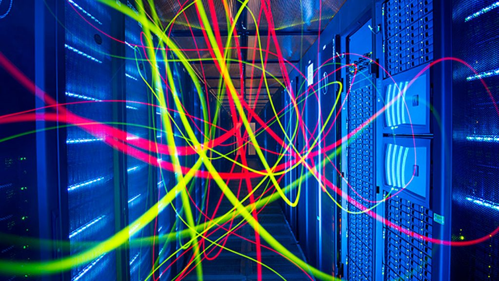Brightly coloured light trails in a blue room full of computer servers