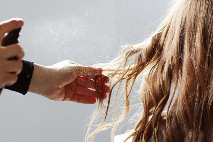 Person spraying hair product onto long, blonde hair