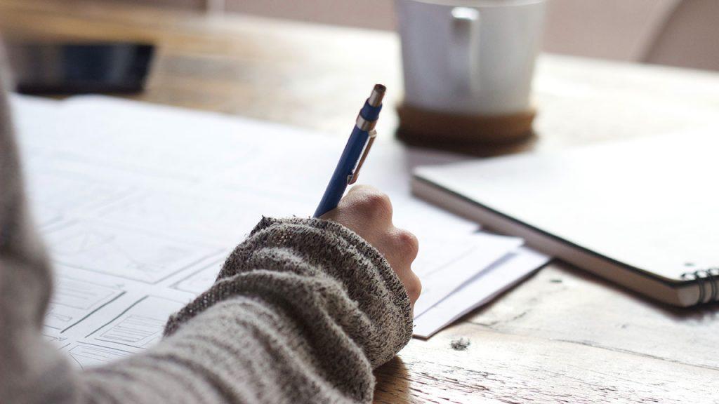 Female hand holding pen writes on notepad